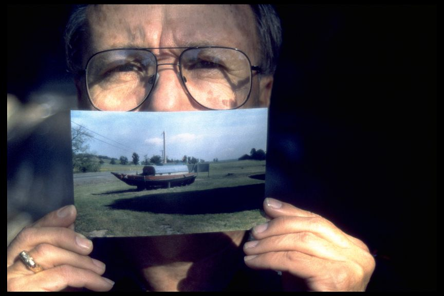 Michael Dee Cookinham holding a photo of the Chinese junk, known as the Haung Ho, which he once owned, now high and dry somewhere in Northern Cal., 1995
